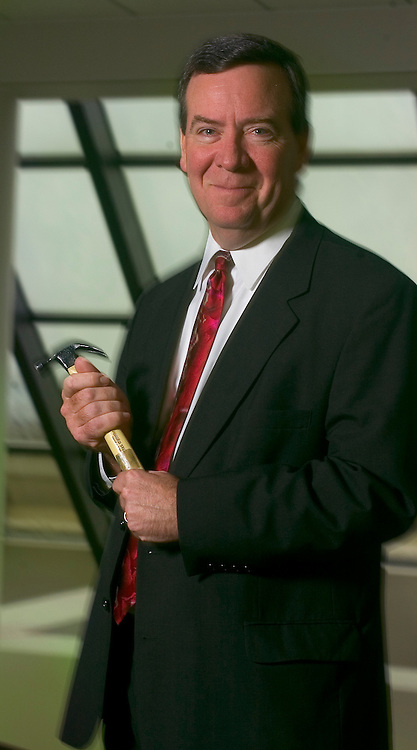 """9/21/06 Omaha NE  Managing Director of Finance for TD Ameritrade Bill Gerber in the lobby of  TD Ameritrade corporate headquarters in Omaha, Neb Thursday morning with his symbolic hammer, that he uses to """"hammer out"""" budgets..(Chris Machian/for Financial Week)"""