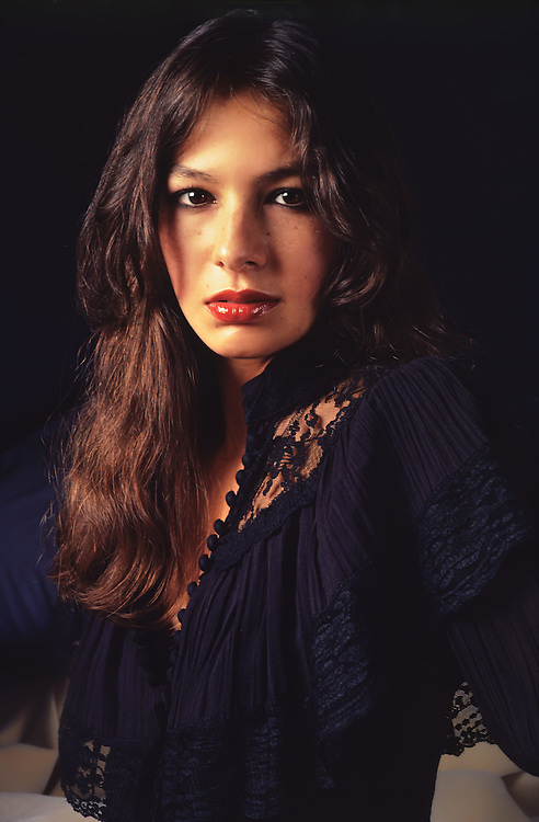 Lesa wearing a lace black blouse looking into the camera. She has long brunette hair with very full shiny lips and very dark eyes.