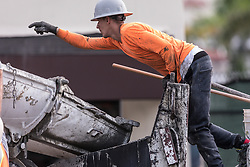 June 16, 2018 - Palm Beach, Florida, USA - A worker guides a truck driver as he backs up to deliver concrete to a boom pump trump during a concrete pour at the old Testa site on Royal Poinciana Way Saturday, June 16, 2018. (Credit Image: © Damon Higgins/Palm Beach Daily News via ZUMA Press)