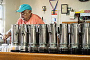 A barista makes a cup of coffee standing behind a stack of  cold brew drip coffee pots in Atotonilco de Alto, Mexico.