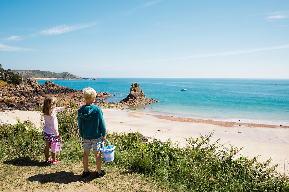 Children holding buckets looking out over the hidden cove Beauport beach on a sunny spring day in Jersey, Channel Islands