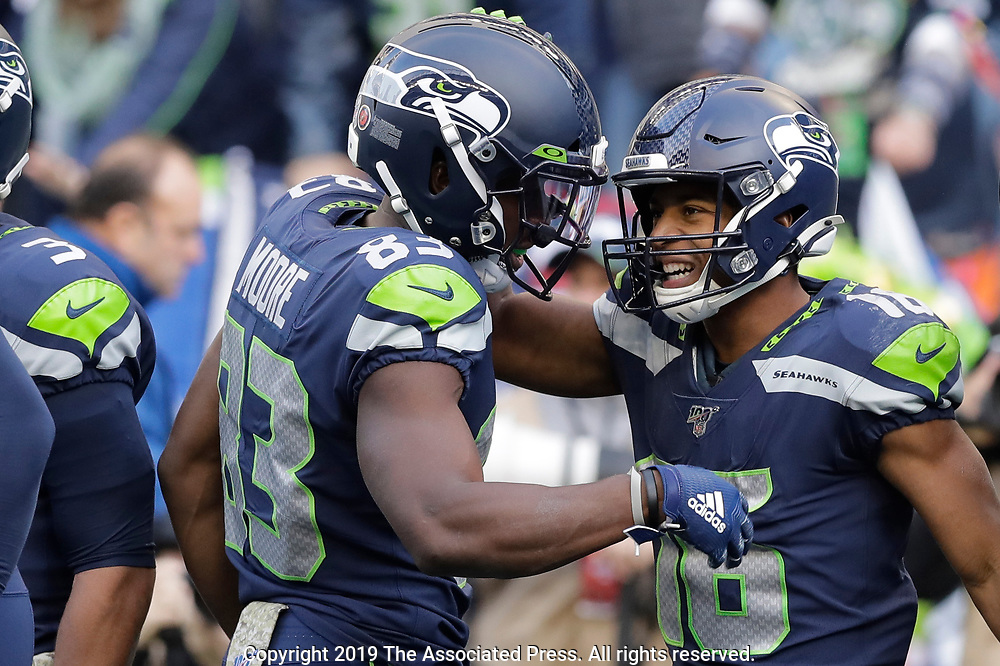 Seattle Seahawks wide receiver Tyler Lockett, right, is greeted by wide receiver David Moore (83) after Lockett scored a touchdown against the Tampa Bay Buccaneers during the second half of an NFL football game, Sunday, Nov. 3, 2019, in Seattle. (AP Photo/John Froschauer)