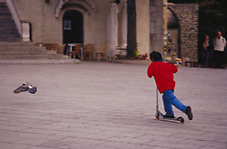 Europe, Italy, Salerno, Ravello. Boy riding scooter in plaza