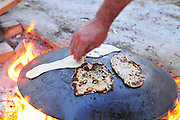 Outdoor Cooking preparing a flat bread Pita on a Saj - an iron dome shaped pan that is used to cook the pita bread on. It is placed over a source of heat, traditionally a wood fire, and the dough is placed on it to cook.