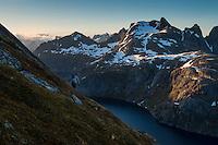 Female hiker descends steep mountain slope from Støvla mountain peak, Moskenesøy, Lofoten Islands, Norway