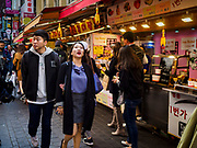 14 OCTOBER 2018 - SEOUL, SOUTH KOREA: People walk past street food stalls in the neighborhood around Myeongdong Street between the Cathedral and City Hall in Seoul. It's a high end shopping, dining and entertainment district, popular with tourists and wealthy South Koreans.      PHOTO BY JACK KURTZ