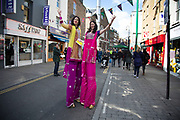 Stilt walkers at an Asian street food festival on Brick Lane, London, JUK. Dressed in pink and yellow sari material these women on stilts pose for a picture.
