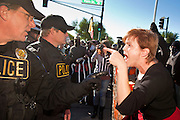 30 NOVEMBER 2011 - PHOENIX, AZ:    An anti-ALEC protester argues with Phoenix police in front of the Westin Kierland Resort and Spa Wednesday. About 300 people picketed the American Legislative Exchange Council (ALEC) conference at the Westin Kierland Resort and Spa in Phoenix, AZ, Wednesday. The protesters claim ALEC, a conservative think tank, violates its tax exempt status by engaging in lobbying, a charge ALEC officials deny. Many conservative pieces of legislation, like Arizona's anti-immigration bill SB1070, originate with ALEC conferences (SB 1070 originated at an ALEC conference several years ago). Many of the protesters are also members of the Occupy movement.   PHOTO BY JACK KURTZ