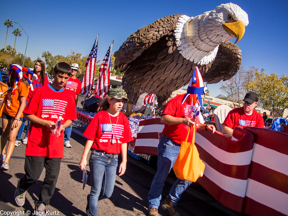 """11 NOVEMBER 2013 - PHOENIX, AZ:  A float of a bald eagle in the Phoenix Veterans Day Parade. The Phoenix Veterans Day Parade is one of the largest in the United States. Thousands of people line the 3.5 mile parade route and more than 85 units participate in the parade. The theme of this year's parade is """"saluting America's veterans.""""     PHOTO BY JACK KURTZ"""