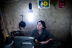 PKK member Necbir Botan, 28, from Turbaci in Syria, makes member's uniform at their sewing workshop in Qandil Mountains, Iraqi Kurdistan. She has been with PKK in Qandil for  four years.