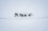 Aerial view of a nordic landscape and road covered with snow in Estonia.
