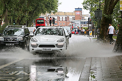 © Licensed to London News Pictures. 27/07/2019. London, UK. A XX splashes water as it drives through a flood on Green Lanes in north London, caused by heavy overnight downpour. Photo credit: Dinendra Haria/LNP
