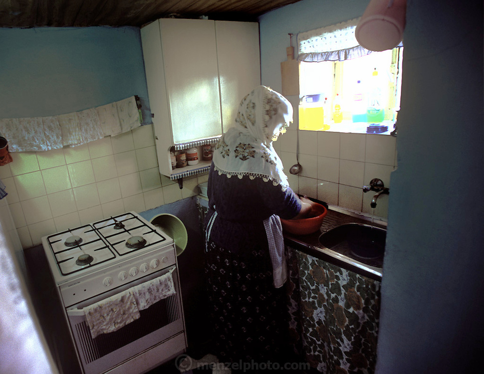 (MODEL RELEASED IMAGE) Feriye Çinar cleans up in the small kitchen of her family's home in the Golden Horn district of Istanbul, Turkey. She and her husband Sezgi moved here with his familiy from the Black Sea region of Turkey to make a better life for their family. (Supporting image from the project Hungry Planet: What the World Eats)
