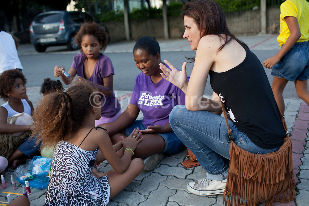 Female volunteer talking to young girls. In April 2014 thousands of people were evicted from Telerj favela in an old building owned by communications company Oi. Having nowhere to go, they camped outside the Central Cathderal in Rio de Janeiro, Brazil. Many of them were children, they received many donations from local people and community groups.