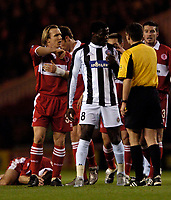 Photo. Jed Wee, Digitalsport<br /> Middlesbrough v Partizan Belgrade, UEFA Cup, 15/12/2004.<br /> Middlesbrough's Boudewijn Zenden (L) alleges the use of an elbow from Partizan's Pierre Boya (C), as Colin Cooper lies injured.
