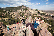 Shawn Olson relaxes with friends on top of a red rock spire in Settlers' Park in Boulder, Colorado.
