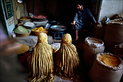 Afghan women bargain with a grain merchant in the Mandawi bazaar, Kabul's busiest open-air market. Both are clad in the burqa — a traditional garment that, in the patriarchal world of Afghanistan, most women still wear in public.  © Steve Raymer / National Geographic Creative