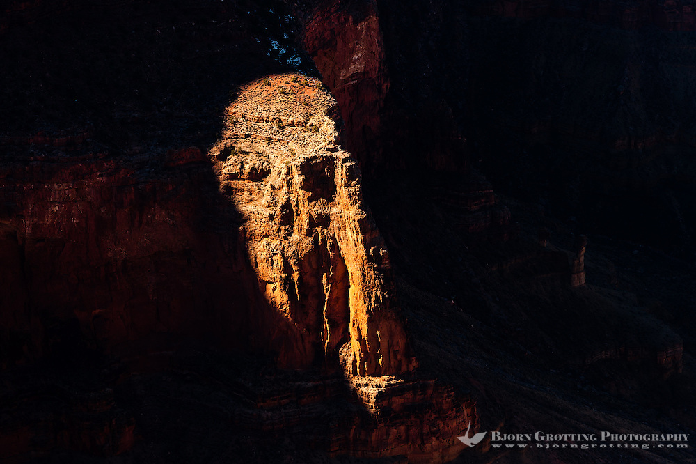 United States, Arizona, Grand Canyon. Mohave Point has a great view of the near vertical cliffs around The Abyss and continuing towards Pima Point. The sunlight hits a protruding part of the dark rock wall.