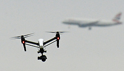 Embargoed to 0001 Saturday July 22 File photo dated 25/02/17 of a drone flying in Hanworth Park in west London, as a British Airways 747 plane prepares to land at Heathrow Airport behind. A drone registration system is to be launched under new rules to reduce misuse, the Government has announced.
