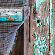 An old screen door shows the history of time after decades of winter and weather abuse in the Teton mountain range near the town of Jackson, Wyoming.