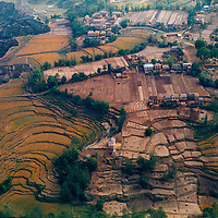 Terraced rice paddies suround a village in the foothills of the Hmalaya in Nepal.