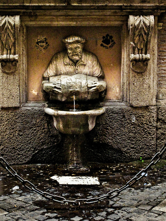 Street fountain in an alley beside the Palazzo Doria Pamphilij, Fontanella del Facchino, 16th century.  Figure of a man, probably a porter, holding a barrel from which the water pours from a hole in its side to fall into a basin below.  Cobbled street, protective chain in front of the figure.