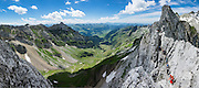 Weaving through limestone outcroppings, we hiked the stunning Lisengrat, a sinuous chain-protected trail from Rotsteinpass to the summit of Säntis. The Lisengrat is a magnificent ridge route between Säntis (2502 m / 8218 feet elevation) and Altmann (2435 m / 7989 ft), the two highest peaks in Appenzell's Alpstein range. The rocky route is safe, but can be scary for those with fear of heights. Shared by three cantons, Säntis can be reached easily via cable car or with effort via trails, to see vast mountain views across six countries: Switzerland, Germany, Austria, Liechtenstein, France and Italy. The Appenzell Alps rise between Lake Walen and Lake Constance. This image was stitched from multiple overlapping photos.