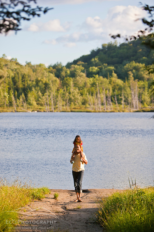 A man and his young daughter walk on a path to Mud Pond in Zack Woods, Hyde Park, Vermont. Green River Reservoir State Park