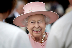 Queen Elizabeth II talks to guests during a garden party at Buckingham Palace in London.