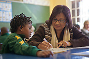 A female teacher shows a young African girl how to write in a classroom in Observatory Primary School, Cape Town, South Africa. The volunteer teachers have been provided to the school by Shine Centre which is a charity that aims to address the high illiteracy rate in South Africa by improving literacy levels among children in schools and disadvantaged communities.