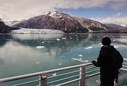 An unidentified tourist on the daily tour boat, Baranof Wind,admires the face of Margerie Glacier, one of the seven tidewater glaciers in Glacier Bay National Park and Reserve in southeast Alaska. The Margerie Glacier is located on the Tarr Inlet next to another tidewater glacier, Grand Pacific Glacier. Margerie Glacier's one mile wide face has a total height of 350 feet, out of which 250 feet is above the water level and 100 feet is beneath the water surface. For comparison purposes the Statue of Liberty is 307 feet tall. The length of the glacier (2011) is approximately 21 miles. The mountain pictured is Mount Forde.
