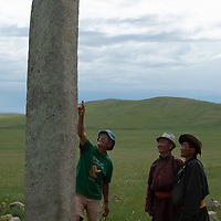Archaeologist Dr. William Fitzhugh points out carvings on a 2700+ year-old, bronze age deer stone to visitors to his site at Ulaan Tolgai,  near Lake Erkhel & Muren, Mongolia. <br /> MS0702_060626_0180.NEF