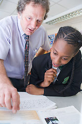 Secondary School teacher explaining data and finding of experiments in a Science lesson to student,