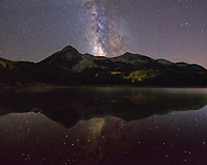 The milky way reflects in Lost Lake in a Colorado autumn night.