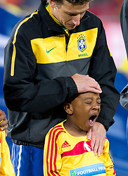Elano warming up little boy during listening to the national anthem at the 2010 FIFA World Cup South Africa Group G match between Brazil and North Korea at Ellis Park Stadium on June 15, 2010 in Johannesburg, South Africa. Brazil defeated Korea 2-1. (Photo by Vid Ponikvar / Sportida)