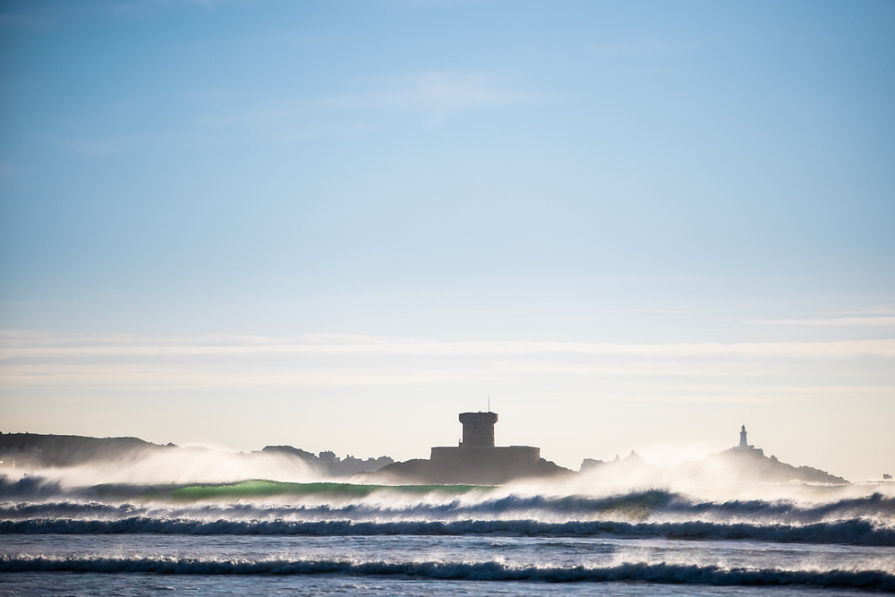 The landmarks La Rocco Tower and Corbiere Lighthouse surrounded by surf and waves breaking on a cold winter afternoon at St Ouen's Bay, Jersey CI
