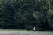 "Woman taking her dog for a walk with her dog ball thrower at hand. Hampstead Heath (locally known as ""the Heath"") is a large, ancient London park, covering 320 hectares (790 acres). This grassy public space is one of the highest points in London, running from Hampstead to Highgate. The Heath is rambling and hilly, embracing ponds, recent and ancient woodlands."