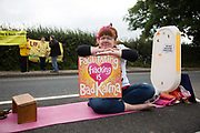 An anti-fracking activist in New Preston Road, July 30 2017, Lancashire, United Kingdom. Facilitating fracking is bad karma. The blockade is a repsonse to the emmidiate drilling for shale gas, fracking, by the fracking company Quadrilla and part of an ongoing struggle where makeshift towers and makeshift camps have sprung up outside the premisses. Lancashire voted against permitting fracking but was over ruled by the conservative central Government. All the activists have been active in the struggle against fracking for years but this is their first direct action of peacefull protesting. Fracking is a highly contested way of extracting gas, it is risky to extract and damaging to the environment and is banned in parts of Europe . Lancashire has in the past experienced earth quakes blamed on fracking.