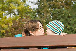 Mother and son kissing each other behind the backrest of park bench in autumn scenery