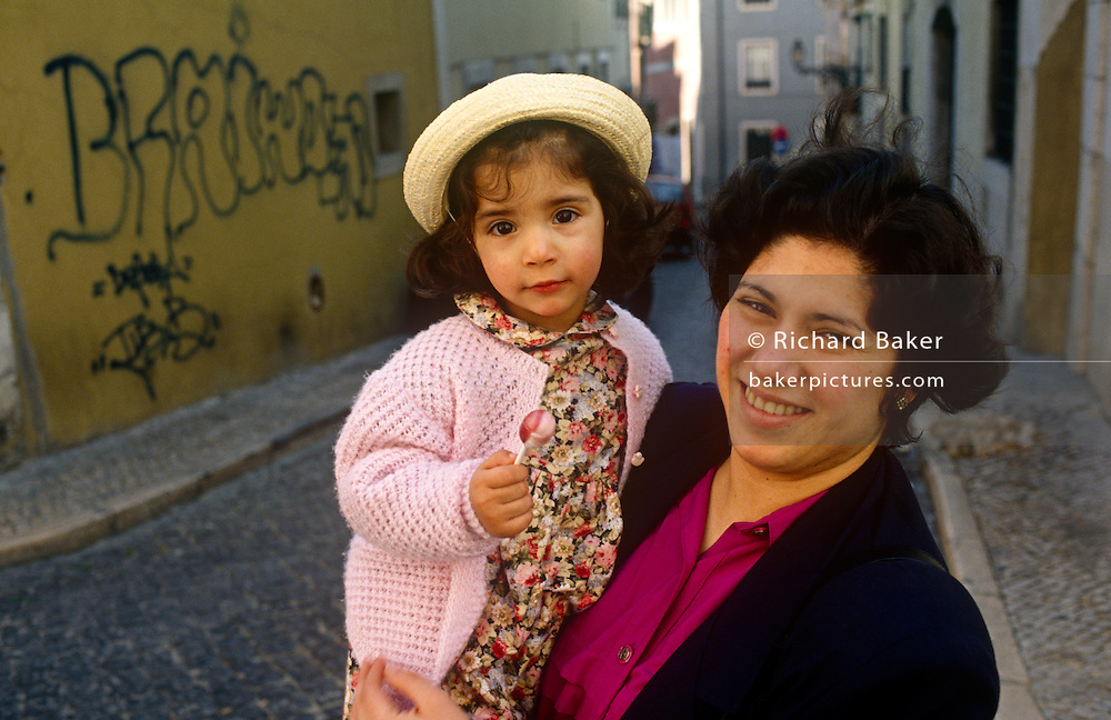 A mother holds her young daughter in a cobbled street of Lisbon's Biarro Alto district.