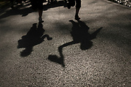 """The shadow of two women carring the baton while running on the 20th Korrika. Erratzu (Basque Country) April 3, 2017. The """"Korrika"""" is a relay course, with a wooden baton that passes from hand to hand without interruption, organised every two years in a bid to promote the basque language. The Korrika runs over 11 days and 10 nights, crossing many Basque villages and cities, totalling some 2300 kilometres. Some people consider it an honour to carry the baton with the symbol of the Basques, """"buying"""" kilometres to support Basque language teaching. (Gari Garaialde / Bostok Photo)"""