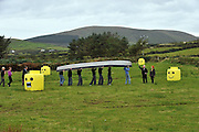 21-9-2012: A curragh hand made by four Colaiste na Sceilge students, Kevin O'Sullivan (Over the Water)  Pierce Lynch (Foilmore) Liam O'Connell (Caherciveen) and Ronan O'Shea (Caherciveen) parade it through field art to be blessed by local priest Fr Padraig Sugrue as part of the Cill Rialaigh 21st celebrations in Ballinskelligs County Kerry..Also in picture are, Stephen O'Connell, Brid Collison, Willie Cronin, Paul Turner, Tadhg Kelly and founder Noelle Campbell Sharp..Picture by Don MacMonagle