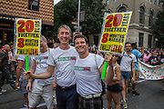 """Jesse Duncan, left, and Marcus Woolen carry signs that read """"20 years together 8 months married finally legal."""" They march with Broadway Impact, an organization of theater artists in support of marriage equality."""