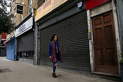 © Licensed to London News Pictures. 22/02/2021. London, UK. A woman walks past closed shops in Haringey, north London, on the day Prime Minister will announce the government's plans for relaxing Covid-19 restrictions in England. Boris Johnson will address the House of Commons at 3.30pm followed by a Downing Street news conference at 7pm. It is expected that shops, restaurants, hairdressers and pubs will reopen mid April. Photo credit: Dinendra Haria/LNP