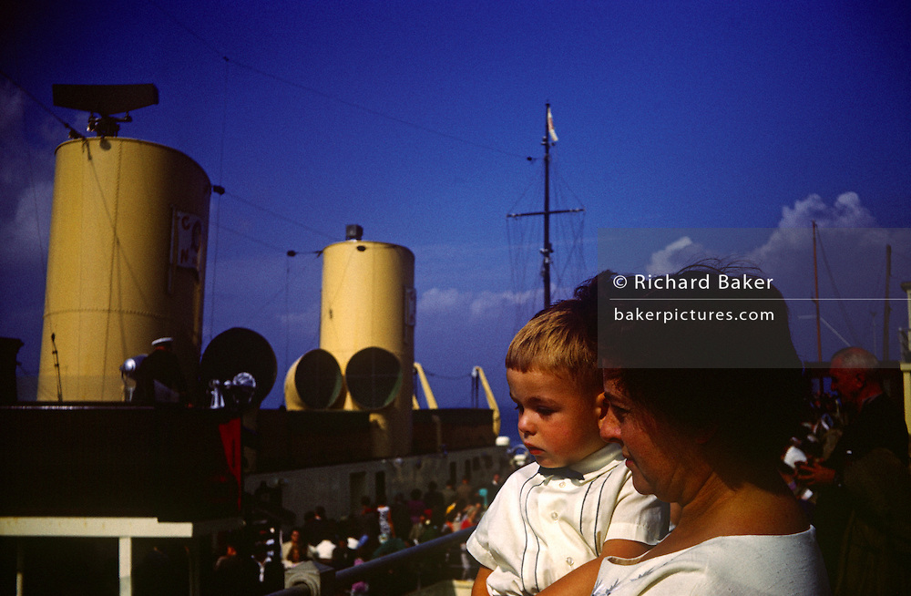 A mother holds her young son up to show him a paddle steamer on Southend pier in the early nineteen sixties.