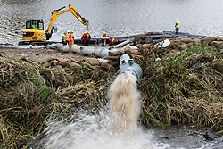 © Licensed to London News Pictures. 05/08/2019. Whaley Bridge, UK. Engineers working on a floating platform in the reservoir connect additional , high-capacity pumping pipes as existing pipes transfer water from the reservoir to a parallel bywater . The town of Whaley Bridge in Derbyshire remains evacuated after heavy rain caused damage to the Toddbrook Reservoir , threatening homes and businesses with flooding . Photo credit: Joel Goodman/LNP