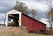"""Crooks Covered Bridge (132 feet long), built 1856 by Henry Wolfe, over Little Raccoon Creek, on Wimmer Road, Parke County, Indiana, USA. Red and white paint protects the wood. """"Cross this bridge at a walk"""" sign requires slow vehicle speed."""