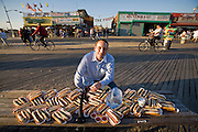 Joey Chestnut, the world's most successful competitive eater, with 66 Nathan's Famous hot dogs and a gallon of water at Coney Island, New York City.  (From the book What I Eat: Around the World in 80 Diets.) This represents what Joey ate (and drank) in 12 minutes on July 4, 2007, to claim the title of world champion hot dog eater. The 66 hot dogs weighed 14.5 pounds and totaled 19,602 calories. MODEL RELEASED.