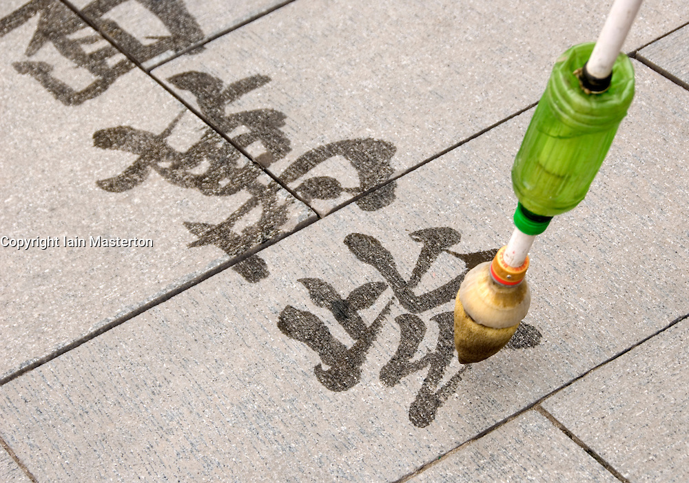 Man drawing Chinese calligraphy with water and paintbrush in Beihai Park Beijing