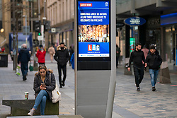 Glasgow, Scotland, UK. 25 November 2020. Glasgow city centre  very quiet during severe level 4 lockdown imposed by the Scottish Government.  Non essential businesses , bars, restaurants and shops are closed. Pictured; Video screen showing news that households can celebrate Christmas together in UK. Credit.  Iain Masterton
